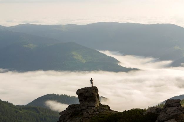 Silhueta de turista alpinista atlético em alta formação rochosa no vale da montanha cheia de nuvens brancas inchadas