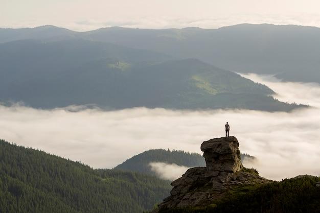 Silhueta de turista alpinista atlético na formação rochosa alta no vale da montanha cheia de nuvens inchadas brancas e nevoeiro e coberto com encostas de montanha verde floresta sob céu claro