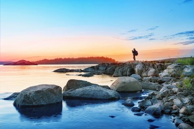 Silhueta de turista com câmera na ilha misteriosa de rochas