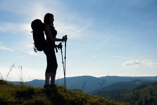 Silhueta de turista magro mulher com mochila e bengalas de pé no topo de uma colina, olhando para longe contra o céu azul de manhã