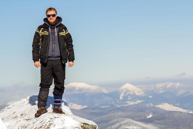 Silhueta de turista sozinho em pé no topo da montanha de neve, apreciando a vista e conquista em dia ensolarado de inverno brilhante. aventura, atividades ao ar livre e conceito de estilo de vida saudável.