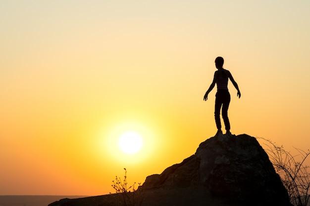 Silhueta de um alpinista de mulher em pé sozinho na pedra grande ao pôr do sol nas montanhas. turismo feminino em pedra alta na natureza de noite. turismo, viagens e conceito de estilo de vida saudável.
