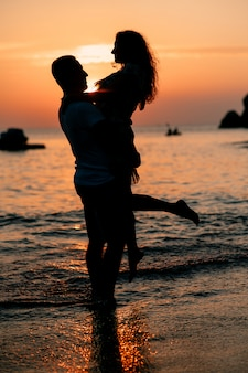 Silhueta de um casal apaixonado ao pôr do sol na praia - um homem segura sua mulher nos braços. relação romântica. lua de mel.