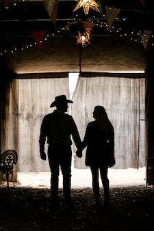 Silhueta de um casal de mãos dadas em uma barraca sob as luzes