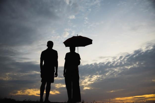 Silhueta de um casal discutindo no pôr do sol / conceito discutindo