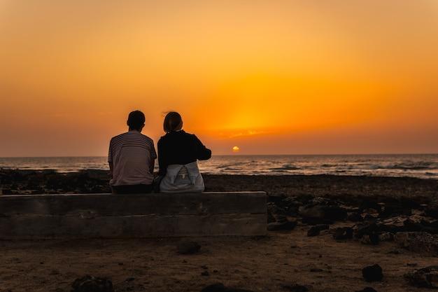 Silhueta de um casal no pôr do sol do farol de toston, punta ballena, perto da cidade de el cotillo, ilha de fuerteventura, nas ilhas canárias. espanha