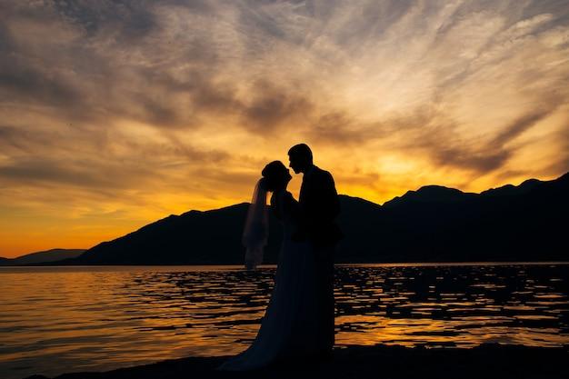 Silhueta de um casal recém-casado ao pôr do sol