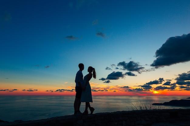 Silhueta de um casal recém-casado no mar em casamento ao pôr do sol em