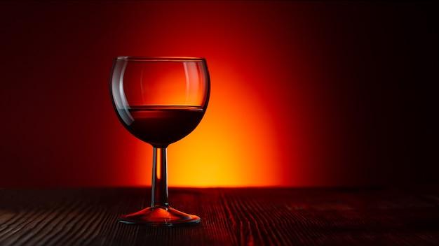 Silhueta de um copo vazio de vinho ou rum em um vermelho escuro iluminado