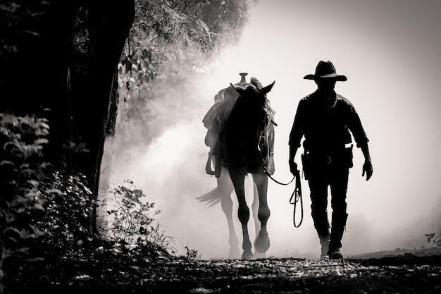 Silhueta de um cowboy e um cavalo no nascer do sol da manhã