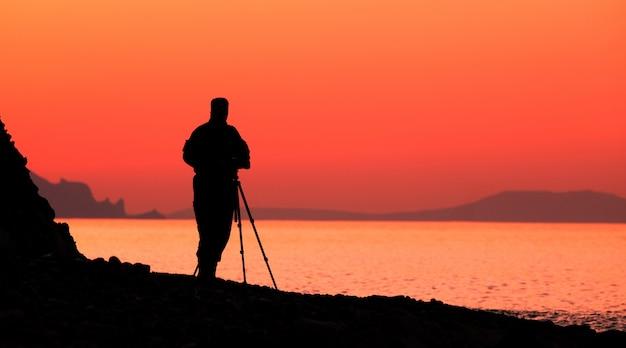 Silhueta de um fotógrafo masculino à beira-mar