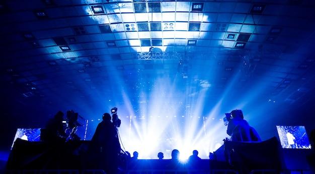 Silhueta de um grupo de cinegrafistas transmitindo um evento. os trabalhadores estão em uma plataforma alta no fundo de vigas brilhantes.