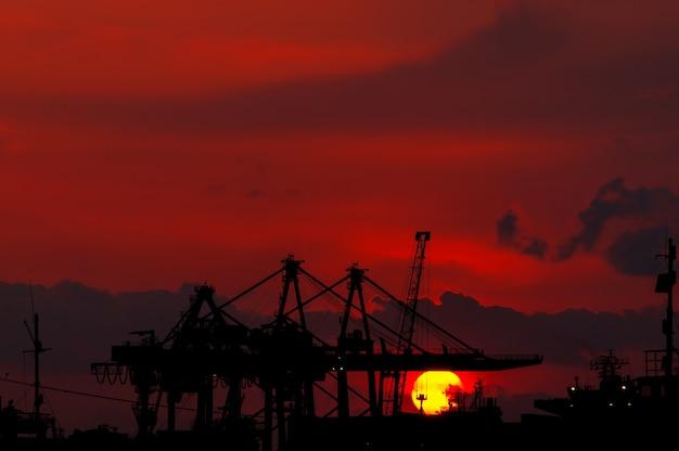 Silhueta de um guindaste industrial descarregando ao pôr do sol. izmir - turquia