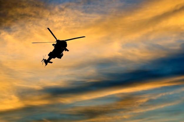 Silhueta de um helicóptero voando contra o céu claro da noite