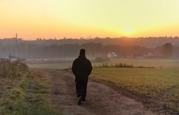 Silhueta de um homem andando no crepúsculo em um caminho em direção ao pôr do sol
