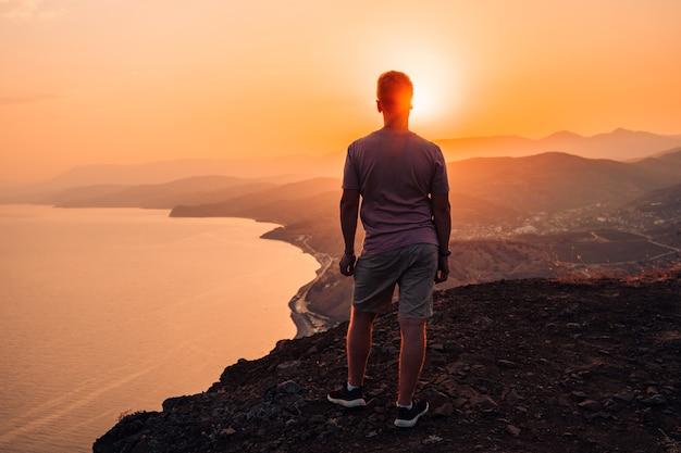 Silhueta de um homem ao pôr do sol em uma falésia com uma paisagem magnífica e vista para o mar.