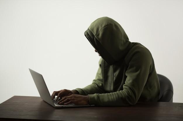 Silhueta de um homem com um capuz sentado à mesa com um laptop