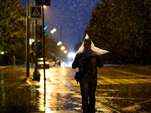 Silhueta de um homem com um saco plástico na cabeça em vez de um guarda-chuva
