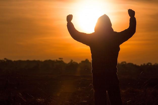 Silhueta de um homem em pé e levante as mãos no ar durante o pôr do sol