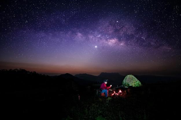 Silhueta de um homem em um acampamento e a beleza da via láctea em doi luang, distrito de chiang dao, província de chiang mai