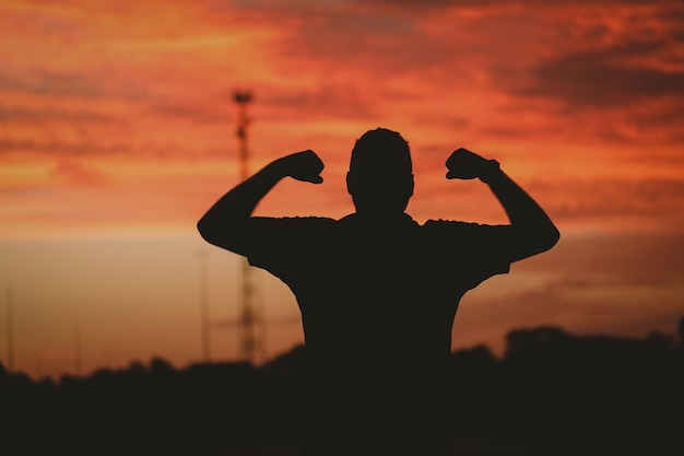 Silhueta de um homem forte sob um céu nublado durante o pôr do sol dourado