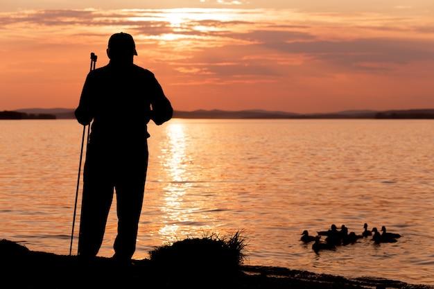 Silhueta de um homem idoso solitário ao pôr do sol alimentando os patos