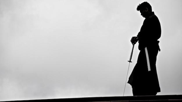 Silhueta de um homem japonês no quimono praticando com uma espada de katana japonesa tradicional