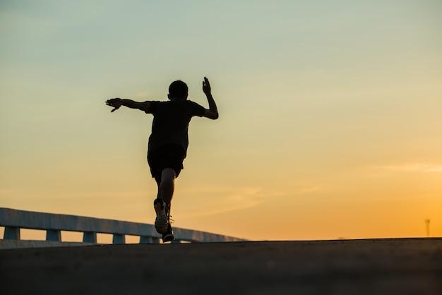 Silhueta de um homem jovem aptidão correndo no nascer do sol