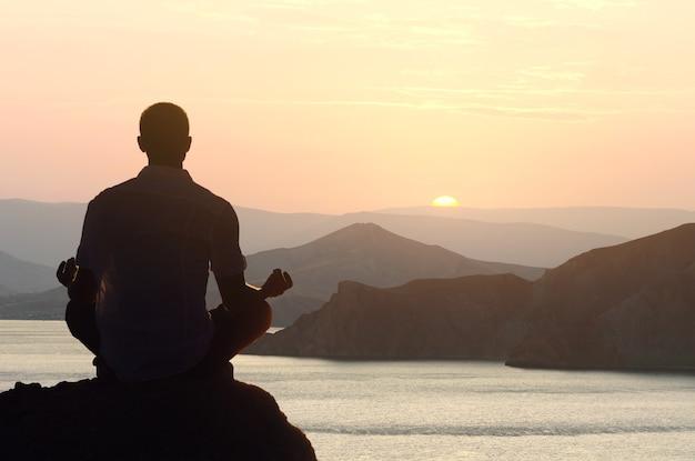 Silhueta de um homem meditando ioga ao amanhecer em posição de lótus à beira-mar