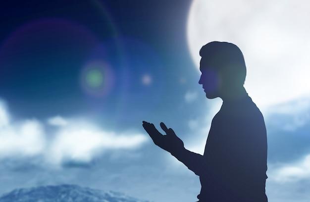 Silhueta de um homem muçulmano em pé enquanto levanta as mãos e ora com a cena noturna de fundo