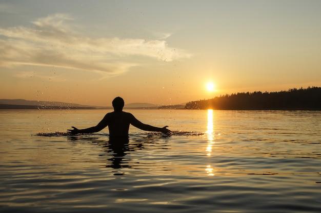 Silhueta de um homem no fundo por do sol. o cara na cintura mergulhou no mar.