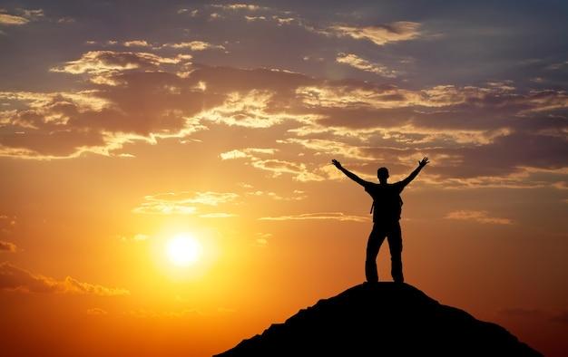 Silhueta de um homem no topo de uma montanha. silhueta de pessoa na rocha. esporte e conceito de vida ativa