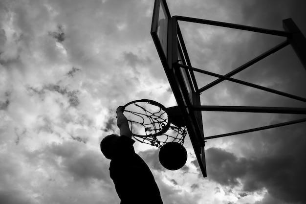 Silhueta de um homem que joga uma bola em uma cesta de basquete na rua contra um céu com nuvens em preto e branco