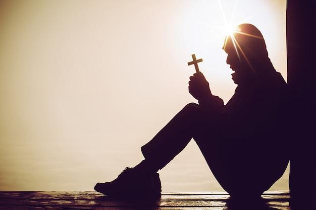 Silhueta de um homem rezando com uma cruz na mão ao nascer do sol.