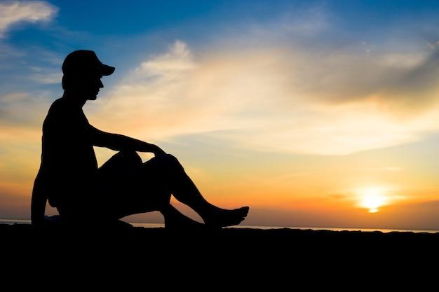 Silhueta de um homem sentado perto do oceano