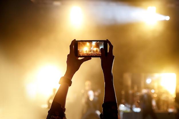 Silhueta de um homem tirando fotos com seu smartphone em um programa de música
