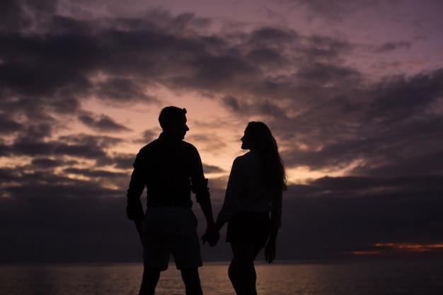 Silhueta de um jovem casal ao pôr do sol na praia perto do oceano