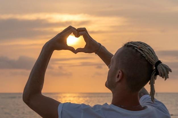 Silhueta de um jovem com dreadlocks na cabeça perto do mar durante o pôr do sol. feche o retrato. homem bonito feliz segurando um formato de coração na praia tropical