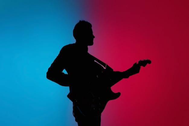 Silhueta de um jovem guitarrista caucasiano isolado em um estúdio gradiente rosa-azulado em luz de néon