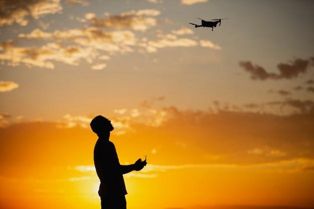 Silhueta de um jovem operando um drone em um cenário rural no pôr do sol