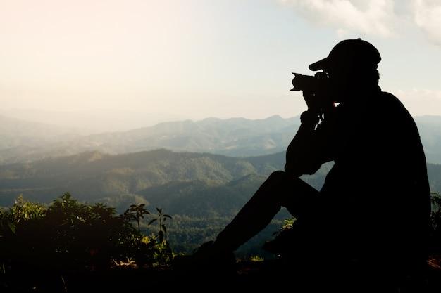 Silhueta de um jovem que gosta de viajar e fotógrafo, tirando fotos dos belos momentos durante o pôr do sol, amanhecer e montanha