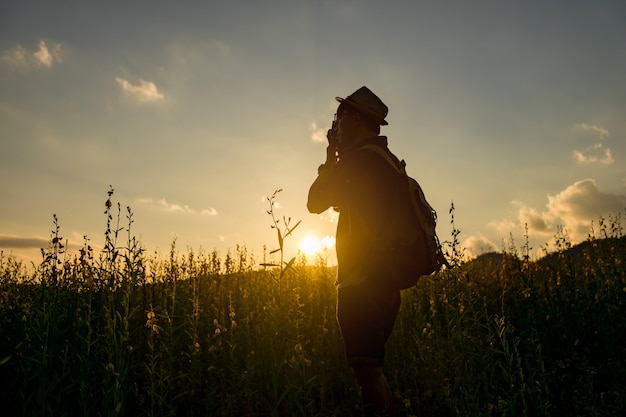 Silhueta de um jovem que gosta de viajar e fotógrafo, tirando fotos dos belos momentos durante o pôr do sol, nascer do sol.