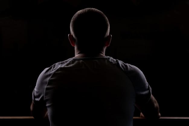 Silhueta de um jovem que se senta. close-up vista por trás. luz de fundo