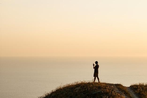 Silhueta de um jovem tirando fotos do mar em um smartphone durante o pôr do sol. noite, verão viagem de férias