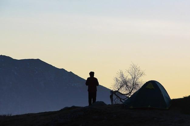 Silhueta de um jovem, uma tenda e uma árvore contra as montanhas