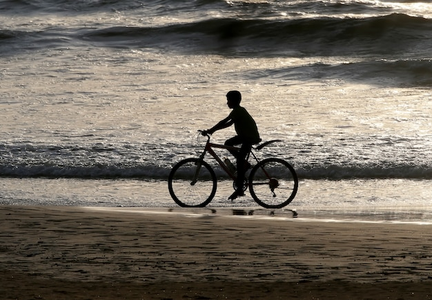 Silhueta de um menino andando de bicicleta ao longo do oceano após o pôr do sol