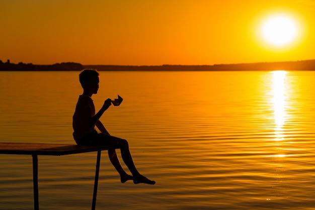 Silhueta de um menino ao pôr do sol, perto do rio.