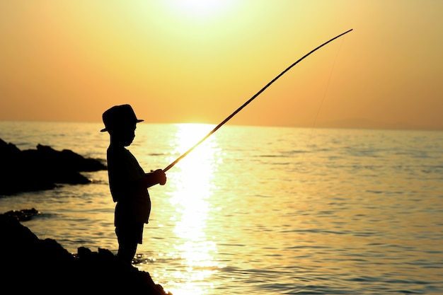 Silhueta de um menino com uma vara de pescar no mar
