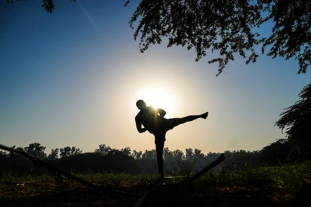 Silhueta de um menino praticando chutes de taekwondo em um parque perto do sol e do rio