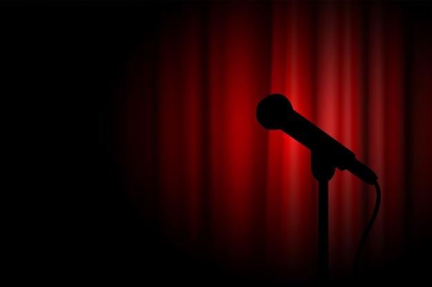 Silhueta de um microfone no palco de atuação com cortina vermelha de teatro